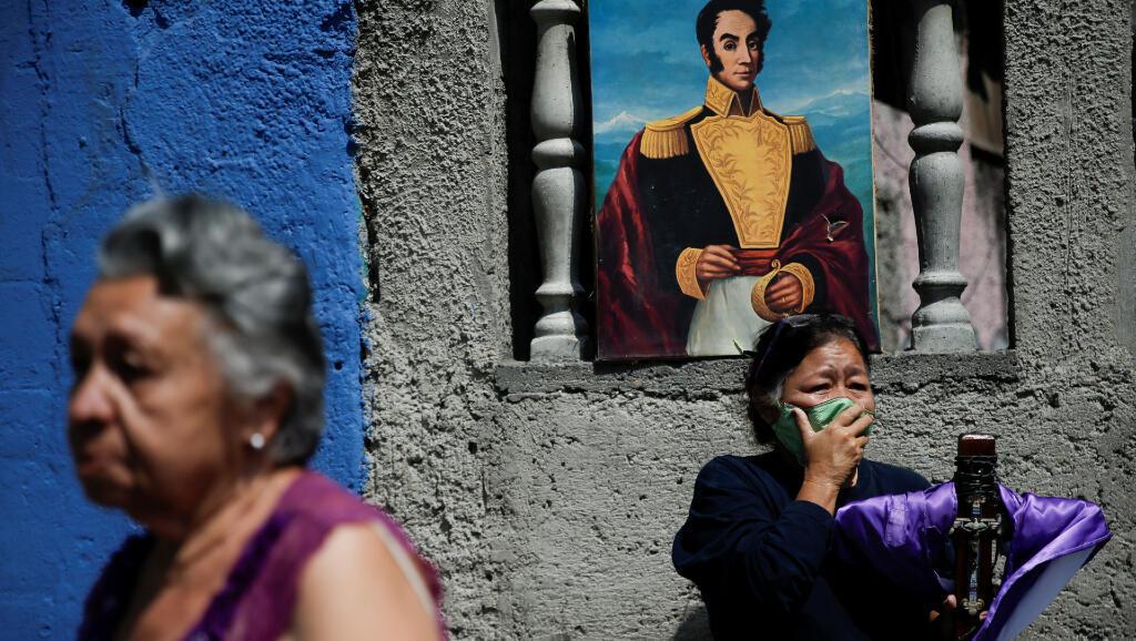 El 8 de abril de 2020, dos mujeres ven una de las procesiones de Semana Santa en Caracas, Venezuela, a pesar del aislamiento obligatorio por causa del Covid-19.