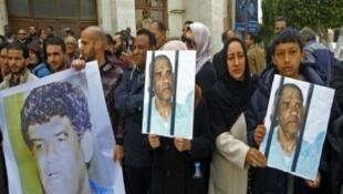 متظاهرون يرفعون صور الرئيس السابق للاستخبارات العسكرية عبدالله السنوسي في طرابلس، ليبيا، 23 مارس/آذار 2019
