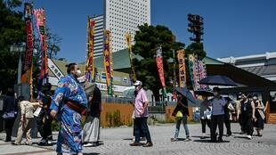 Un sumotori et une file d'attente  devant l'entrée du Ryogoku Kokugikan, principale arène de sumo de Tokyo, le 19 juillet 2020