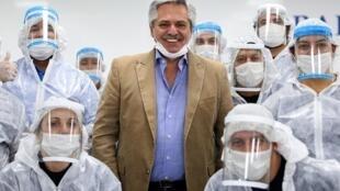 Foto divulgada por la presidencia argentina del mandatario Alberto Fernández (C) posando con trabajadores de una industria automotriz que ahora fabrica barbijos y gorras para luchar contra la propagación del nuevo coronavirus, en las afueras de Buenos Aires, el 1 de mayo de 2020.