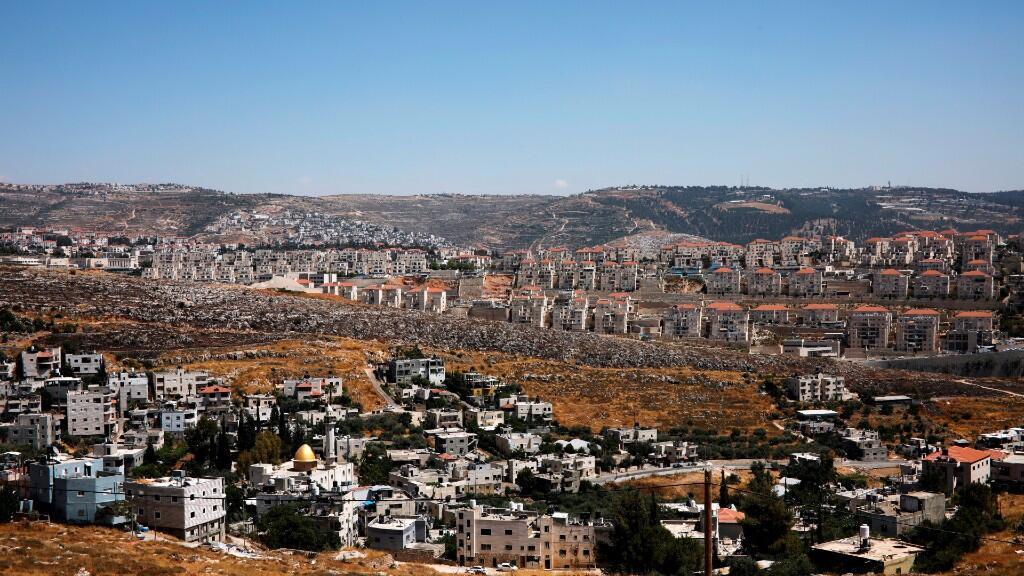 Una vista general muestra casas palestinas en la aldea de Wadi Fukin mientras se ve el asentamiento israelí de Beitar Illit en el fondo. Beitar Illit fue construido en la década de 1990 para los judíos ultra ortodoxos de Israel y es uno de los asentamientos más grandes y de más rápido crecimiento en Cisjordania. 19 de junio de 2019.