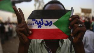 """صورة لشاب سوداني وهو يرفع علم بلاده الذي كتب عليه """"مدنية بس"""" في إشارة إلى رفض الشباب للمجلس العسكري السوداني"""