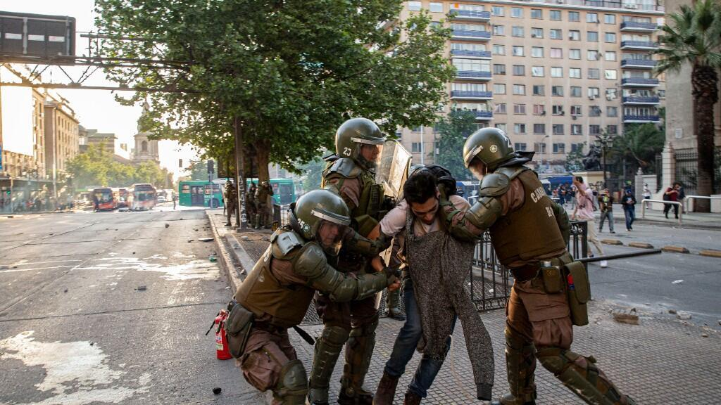 Policías chilenos detienen a un hombre durante una protesta contra el aumento del costo del metro y el autobús, cerca de la estación de metro Santa Lucía en Santiago, el viernes 18 de octubre de 2019.