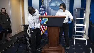Cleaning staff disinfect the lectern in the White House Press Briefing Room