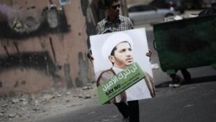 متظاهر يرفع صورا للشيخ علي سلمان في 12 حزيران/ يونيو 2015