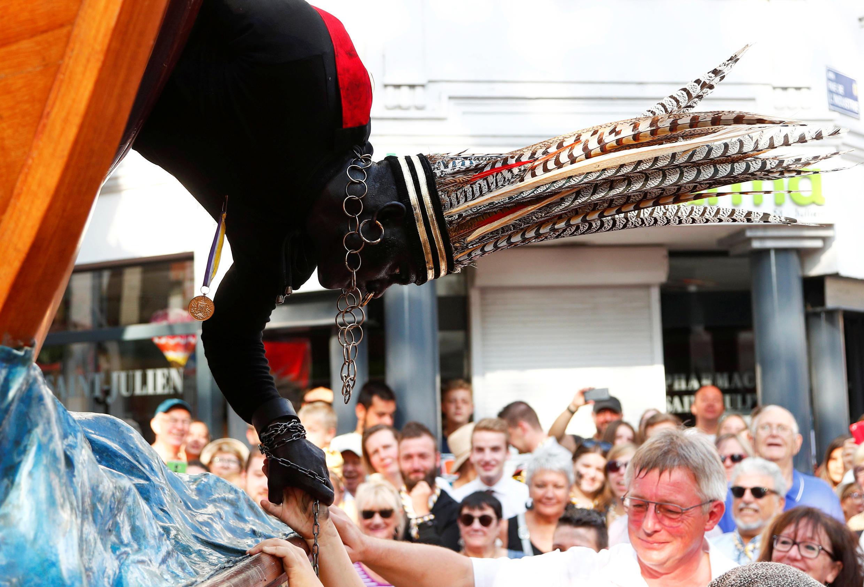 """""""El salvaje"""", un intérprete blanco disfrazado de negro, se inclina para animar a la multitud durante el festival Ducasse d'Ath, en la ciudad occidental de Ath, Bélgica, el 25 de agosto de 2019."""