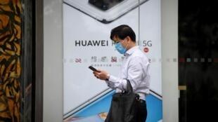Un homme portant un masque de protection passe devant une affiche publicitaire pour Huawei, le 16 mai 2020 à Pékin