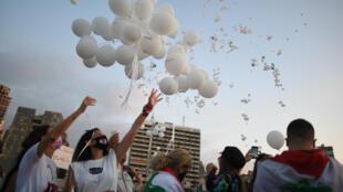 تجمع لعائلات ضحايا انفجار مرفأ بيروت في 4 أكتوبر/تشرين الأول، أي بعد مرور شهرين عن الحادث والمشاركون يطلقون بالونات في سماء بيروت