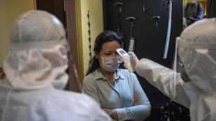 Un funcionario sanitario turco toma la temperatura a una residente de Estambul, el 7 de mayo de 2020