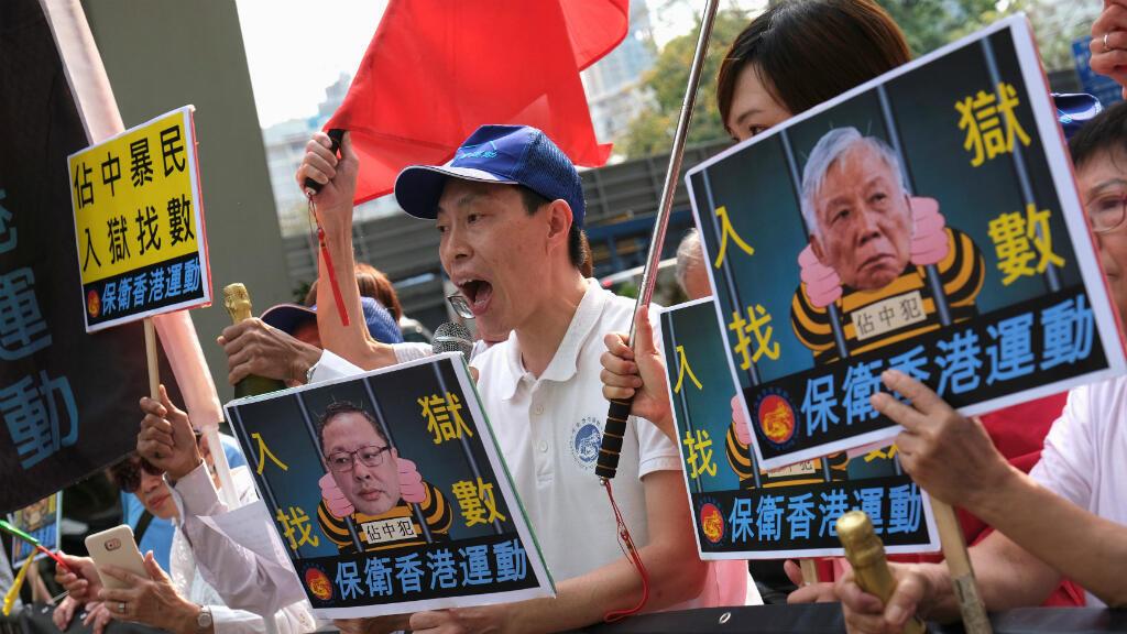 Partidarios de la postura del Gobierno chino apoyan una bandera nacional y una foto de los fundadores de la 'Revolución de los paraguas', Benny Tai y Chu Yiu-ming, fuera de la corte en Hong Kong, China, el 9 de abril de 2019.