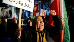 """Los opositores del presidente iraní Hasan Rouhani realizan una protesta frente a la embajada iraní en Roma, Italia, el 2 de enero de 2018. La pancarta dice: """"¡Valiente iraní! ¡Mujahideen es tu amigo! ¡El fuego será tu batalla!"""""""
