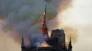 The Notre Dame spire succumbs to the flames on April 15