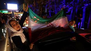 Deux femmes agitent le drapeau iranien lors des célébrations de l'accord sur le nucléaire, à Téhéran, le 14 juillet 2015.