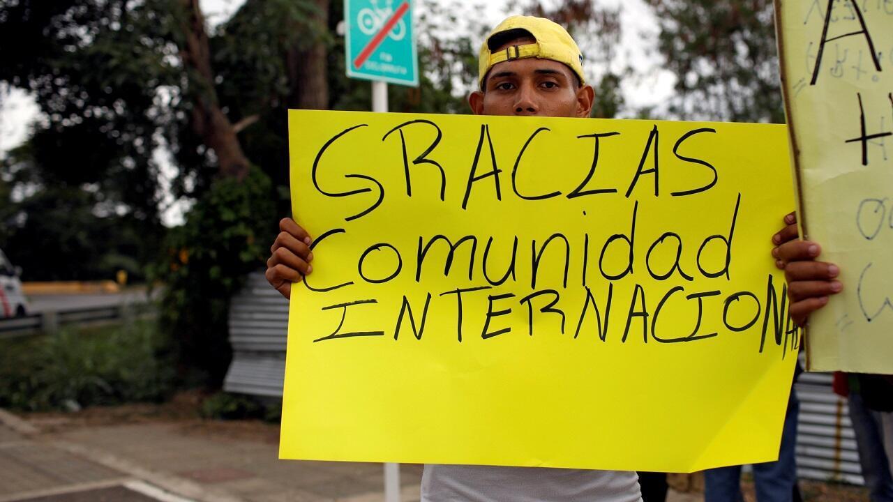 """Un hombre sostiene una pancarta que dice """"Gracias comunidad internacional"""" cerca de un almacén donde se está almacenando la ayuda humanitaria para Venezuela, cerca del puente fronterizo entre Colombia y Venezuela conocido como Tienditas, el 8 de febrero de 2019."""