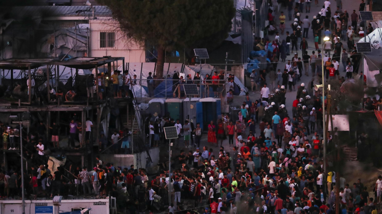 La policía antidisturbios y los migrantes son vistos cerca de contenedores quemados después de un incendio en el campamento de Moria en la isla de Lesbos, Grecia, el 29 de septiembre de 2019.