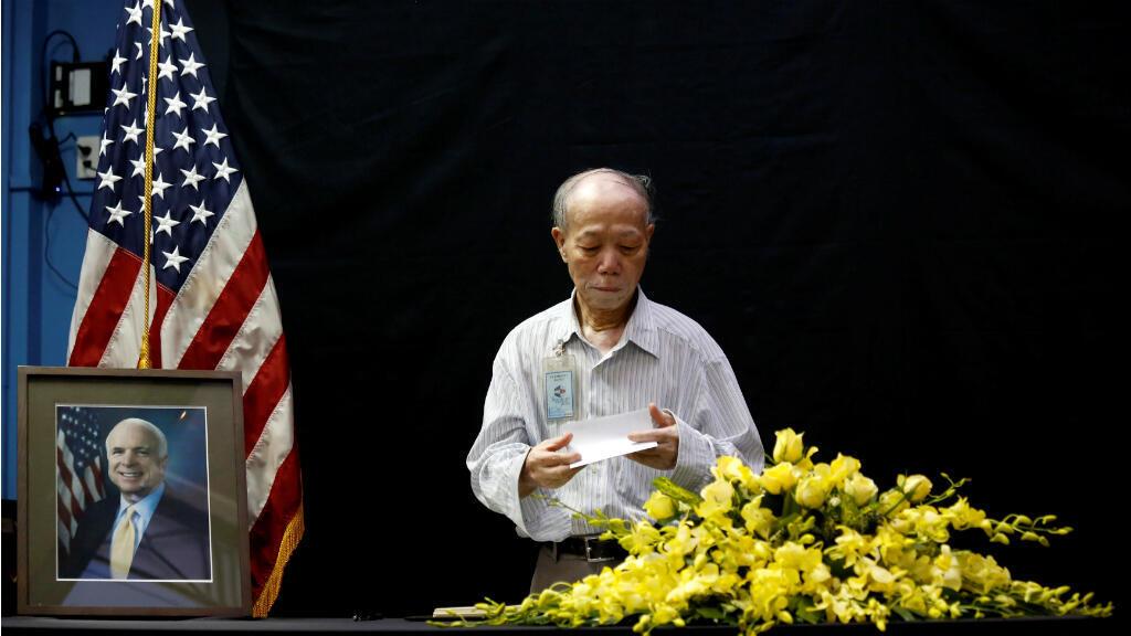 El veterano vietnamita Pham Minh Chuc, de 81 años, le rinde respeto al fallecido senador John McCain después de escribir en un libro de condolencias cerca de un retrato del congresista sobre su muerte en la embajada de los Estados Unidos en Hanoi, Vietnam, el 27 de agosto de 2018.
