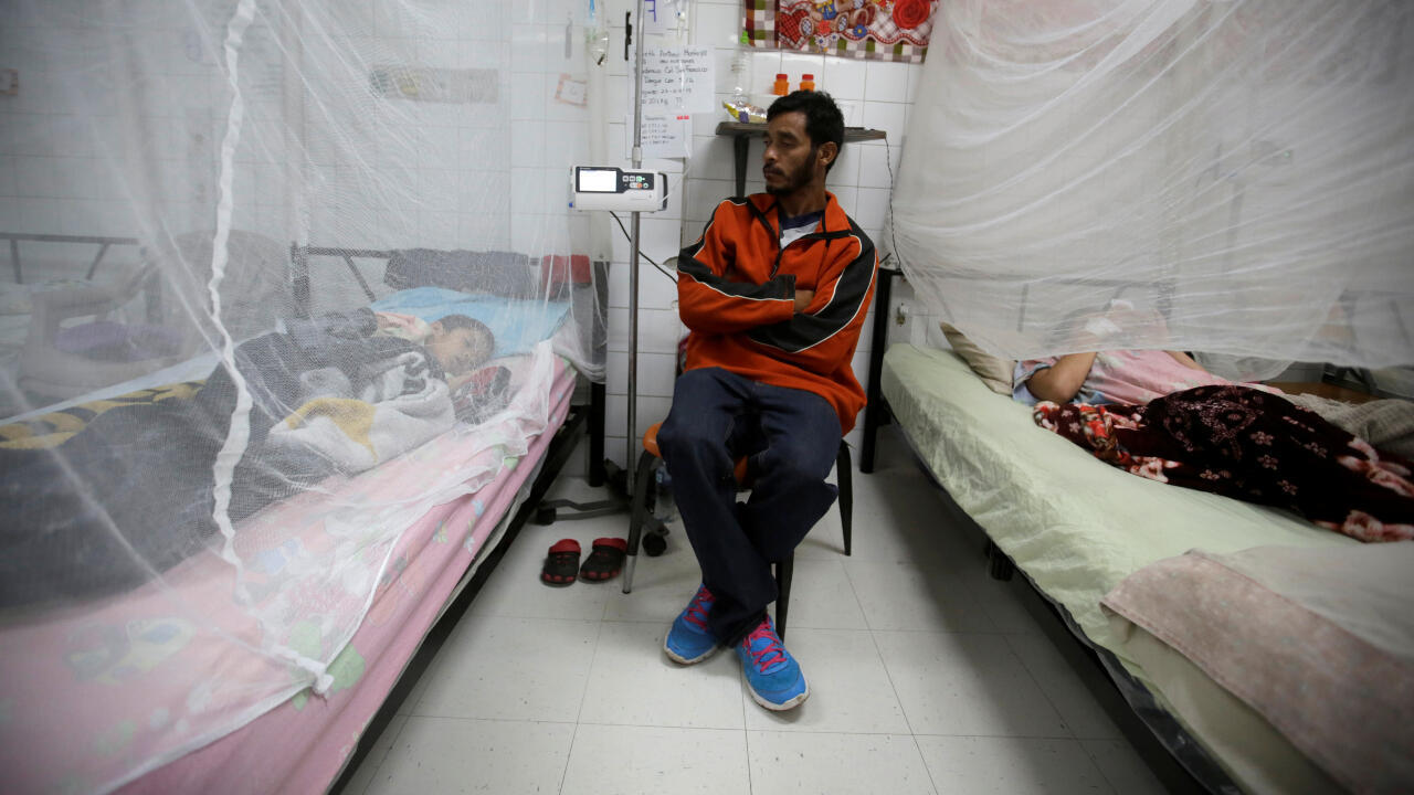 Un hombre se sienta junto a su hijo, hospitalizado por sufrir dengue en Tegucigalpa, Honduras.