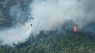 طائرة مكافحة للحرائق ترش المياه على الحرائق التي تلتهم منطقة يستي في جنوب شرق إسبانيا في 28 تموز/يوليو 2017