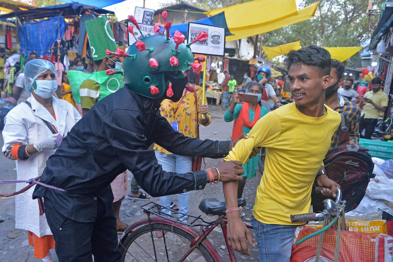 Un hombre de una organización no gubernamental (ONG) con un atuendo que representa al coronavirus Covid-19 se mueve por un mercado instando a las personas a seguir los protocolos de seguridad durante una campaña de sensibilización celebrada en Siliguri, India,  el 25 de abril de 2021.