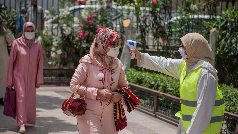 Mujeres hacen fila para medirse la temperatura antes de ingresar a la mezquita Mouline Rabat, Marruecos, 15 de julio de 2020.