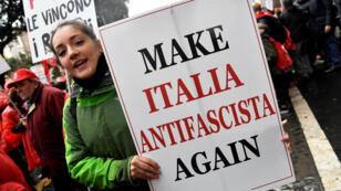 Une femme porte une pancarte lors d'une manifestation antifasciste à Rome, le 24 février 2018, une semaine avant les législatives.