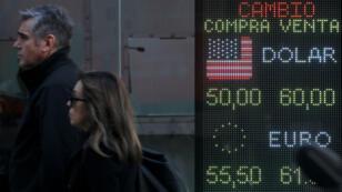 Archivo-Peatones pasan frente a un tablero electrónico que muestra los tipos de cambio en Buenos Aires, Argentina, el 12 de agosto de 2019.