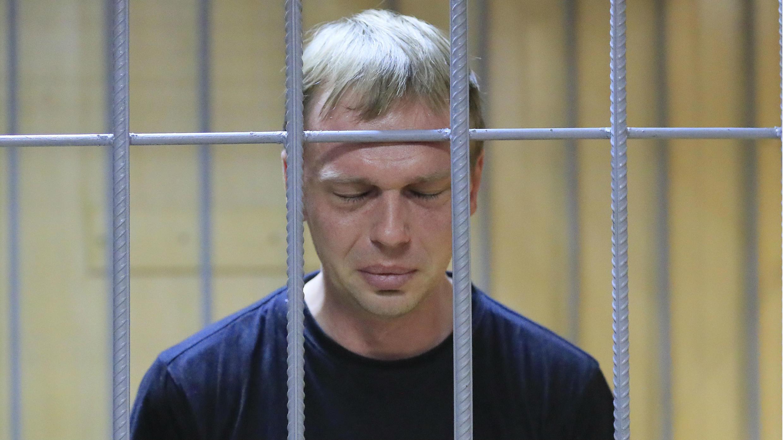 """El periodista de investigación ruso Ivan Golunov, quien fue detenido por la policía y acusado de delitos relacionados con las drogas, reacciona dentro de la jaula de los acusados cuando asiste a una audiencia en el tribunal en Moscú, Rusia, el 8 de junio de 2019. El escrito en la camiseta dice """"Exigencias del mostrador editorial sangre""""."""