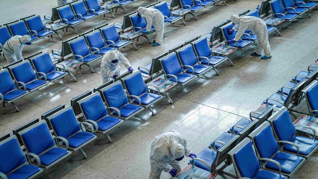 Trabajadores de la limpieza, con trajes de protección, desinfectan una sala de espera en la estación de tren de Wuhan que lleva cerrada varias semanas a causa del brote de  coronavirus, en Wuhan, provincia de Hubei, China, el 24 de marzo de 2020.