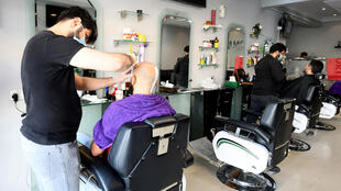Barbers give hair cuts to customers as Qatar gradually lifts Covid-19  restrictions