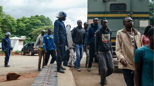 La police anti-émeute zimbabwéenne surveille des hommes arrêtés lors de violentes manifestations déclenchées par la hausse soudaine du prix de l'essence annoncée par le président zimbabwéen.