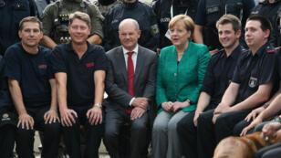 Olaf Scholz et Angela Merkel entouréS de policiers à l'issue du G20 à Hambourg, en juillet 2017.