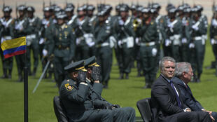 El presidente colombiano Iván Duque (2do-R) y el ministro de Defensa, Guillermo Botero (R) asisten a una ceremonia para el reconocimiento del comando de las Fuerzas Militares en la Escuela Militar José María Córdova en Bogotá el 17 de diciembre de 2018.