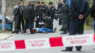 Les policiers examinent le corps du journaliste Oles Bouzina, abattu à Kiev le 16 avril.