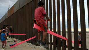 En esta foto tomada el 28 de julio de 2019, las familias estadounidenses y mexicanas juegan con un juguete llamado 'sube y baja' (columpio) sobre la frontera mexicana con Estados Unidos, en la zona de Anapra en Ciudad Juárez, estado de Chihuahua, México.