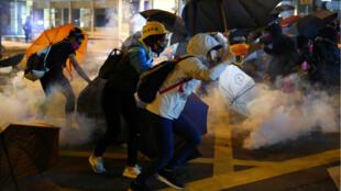 متظاهرون يحاولون الهرب من الغاز المسيل للدموع الذي أطلقته قوات الأمن داخل حرم الجامعة في هونغ كونغ. 18 نومفبر/ تشرين الثاني 2019.