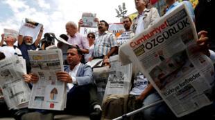 Des militants turques de la liberté d'expression lisent le journal Cumhuriyet en solidarité avec les journalistes condamnés de ce quotidien.