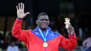El luchador cubano Mijaín López celebra en lo más alto del podio tras obtener su quinta medalla de oro en unos Juegos Panamericanos, en el coliseo Miguel Grau, en Lima, Perú, el 8 de agosto de 2019.