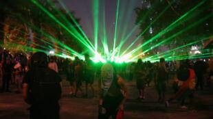 Manifestantes usan rayos láser para evitar que a fuerza pública los disperse en una nueva jornada de manifestaciones en Santiago de Chile el viernes 22 de noviembre de 2019