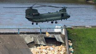 Un helicópetro de la Fuerza Aérea Real de Reino Unido coloca sacos de arena para reforzar la estructura de la represa de ToddBrook. Whaley Bridge, Derbyshire, Inglaterra el 3 de agosto de 2019.