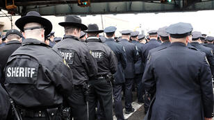 Police officers turn their backs as New York Mayor Bill de Blasio speaks during the funeral of slain New York City Police Officer Wenjian Liu.