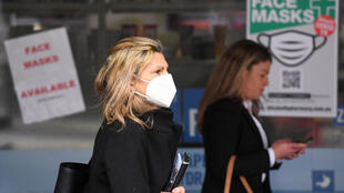 Una mujer con mascarilla pasa por delante de unos carteles el 20 de julio de 2020 en Melbourne
