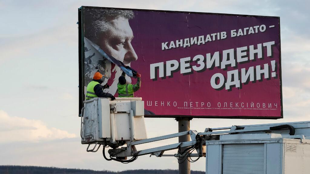 Trabajadores municipales retiran una valla electoral del presidente Petro Poroshenko en Sloviansk, Ucrania, el 28 de marzo de 2019.