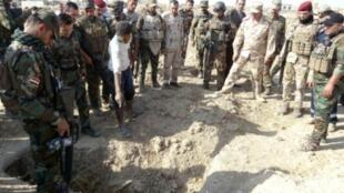 قوات الأمن العراقية أمام مقبرة جماعية في الحويجة، تشرين الثاني/نوفمبر 2017