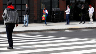 People wait in a socially distanced line outside a supermarket in New York City on April 14, 2020.