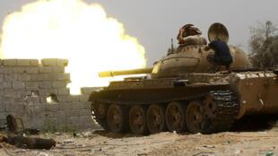 مقاتلون ليبيون موالون لحكومة الوفاق الوطني يطلقون النار من دبابة أثناء القتال ضد القوات الموالية للمشير خليفة حفتر، في جنوب العاصمة الليبية طرابلس، في 13 حزيران/يونيو2019.