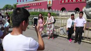 Des touristes chinois se prennent en photo devant le portrait géant de Mao Zedong, place Tiananmen à Pékin, où repose son corps embaumé, le 8 septembre 2016.