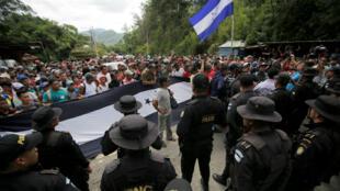 Los oficiales de policía de Guatemala detienen a los migrantes hondureños, integrantes de una caravana que intenta llegar a Estados Unidos, el 15 de octubre de 2018.