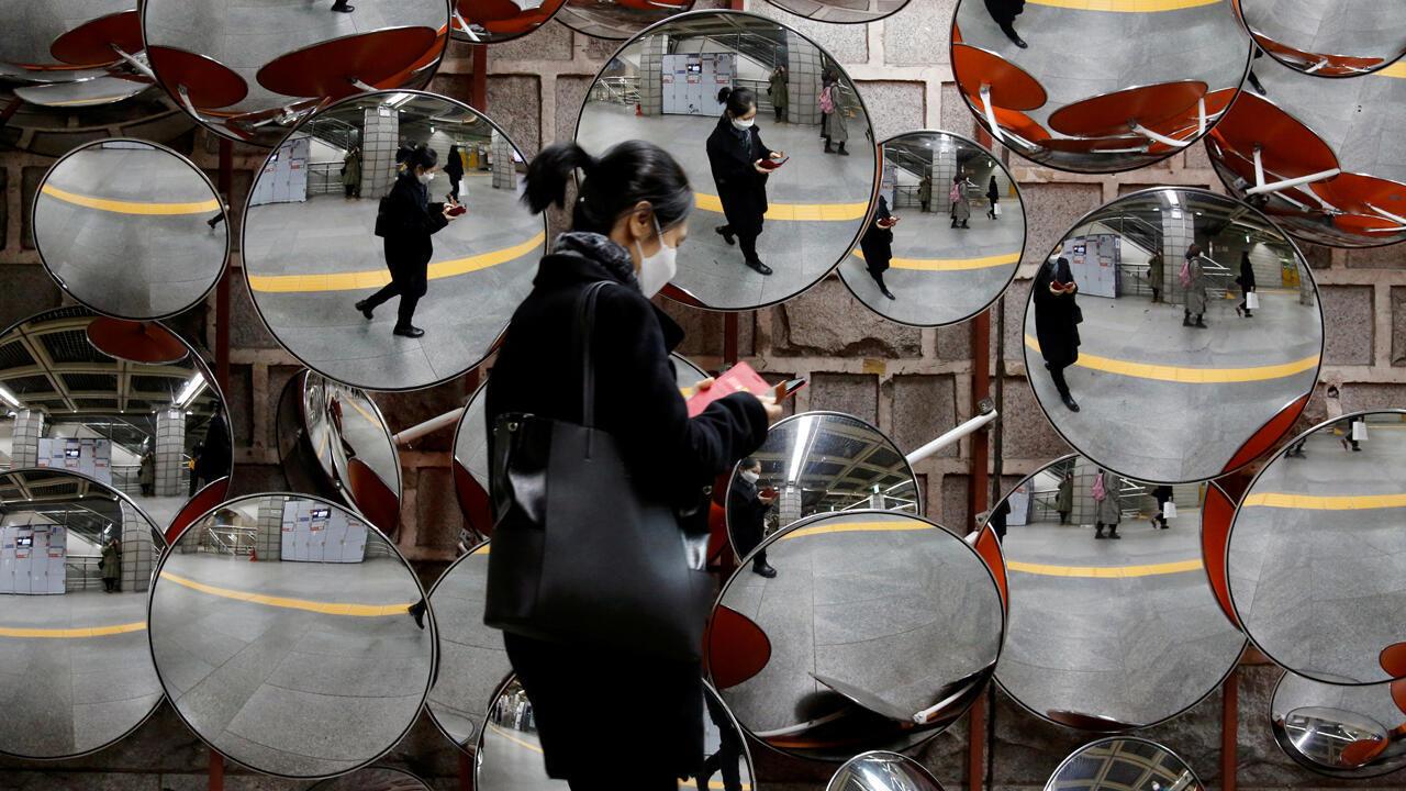 Una mujer se refleja en los espejos, en Seúl, Corea del Sur, el 24 de febrero de 2020.