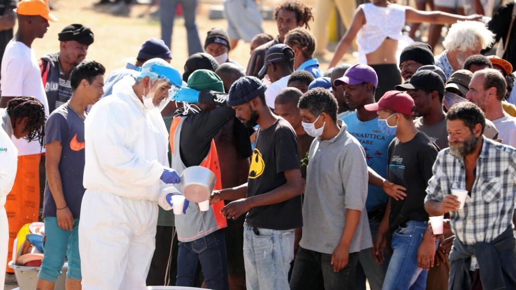 Personas sin hogar hacen fila para recibir comida en un campo habilitado por las autoridades durante los 21 días de aislamiento decretados en Sudáfrica. Ciudad del Cabo, 9 de abril de 2020.