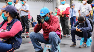 Un grupo de personas hace cola frente a un banco para recibir bonos de ayuda del Gobierno de Perú para paliar la crisis generada por la pandemia de coronavirus, el 15 de junio de 2020 en la ciudad amazónica de Iquitos